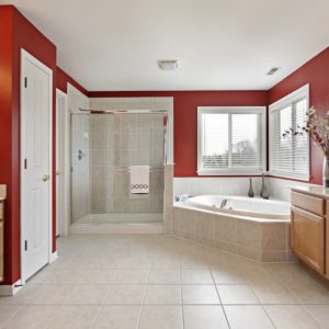 A lovely master bathroom with a corner bathtub and red walls.