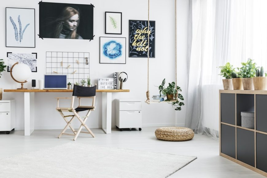 A bright home office with white walls and flooring.