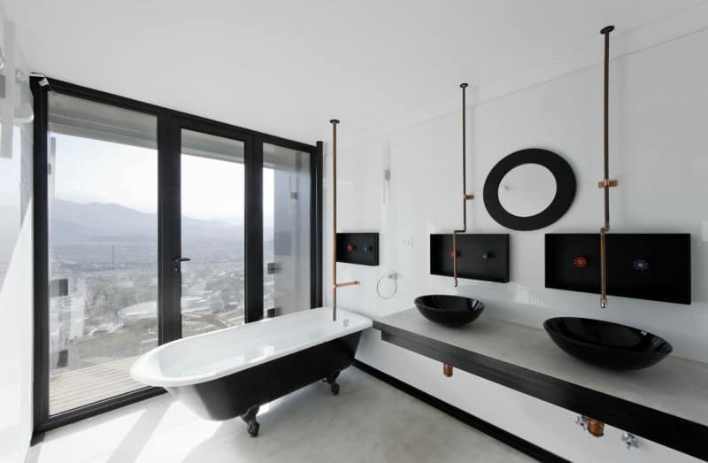 This primary bathroom featuring a floating black vanity hangs next to a clawfoot tub and a tall vase over tiled flooring.