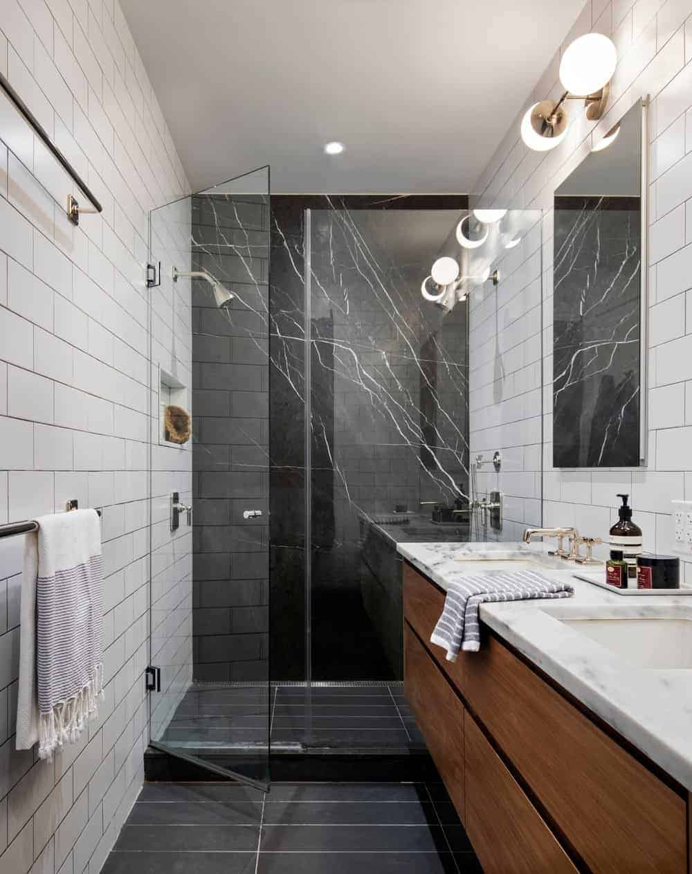 There's a dual sink vanity on the side fitted with cabinets and a walk-in shower enclosed in the glass door. It also has a black and white tiled wall.