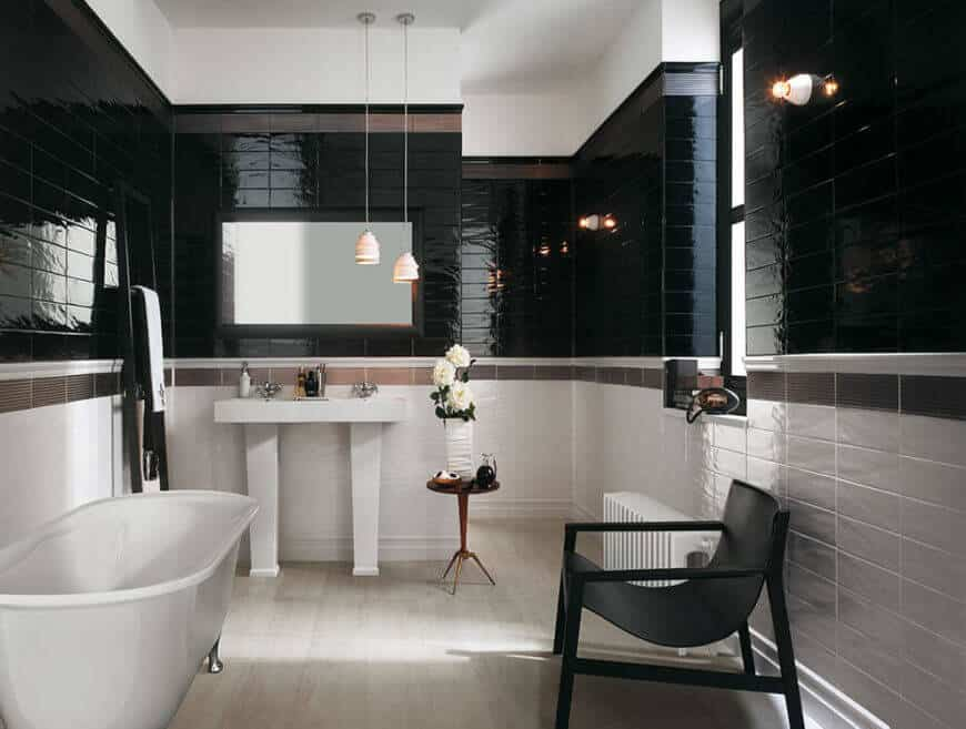 This modestly sized bathroom is tiled in white, brown, and black. The lower half of the room is white, with a strip of brown tile separating the black tile from the white. The result is a gorgeous, sophisticated bathroom that is resistant to mildew and mold.