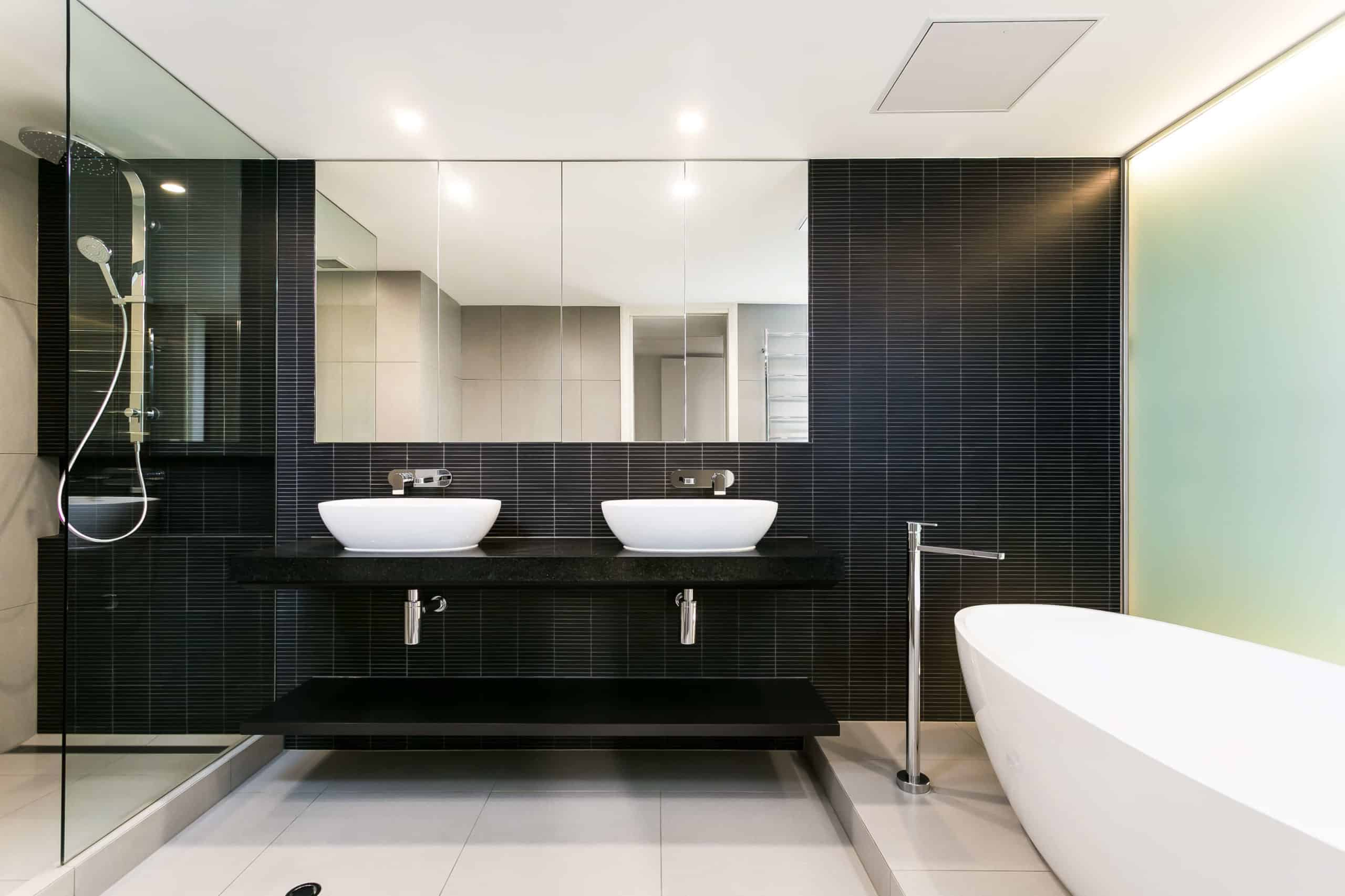 The primary bath hosts a high contrast mixture of tones, with black tiled wall over off-white large format beige floor tiling, plus white pedestal tub and vessel sinks. The floating black vanity hangs next to a large glass-enclosed shower.