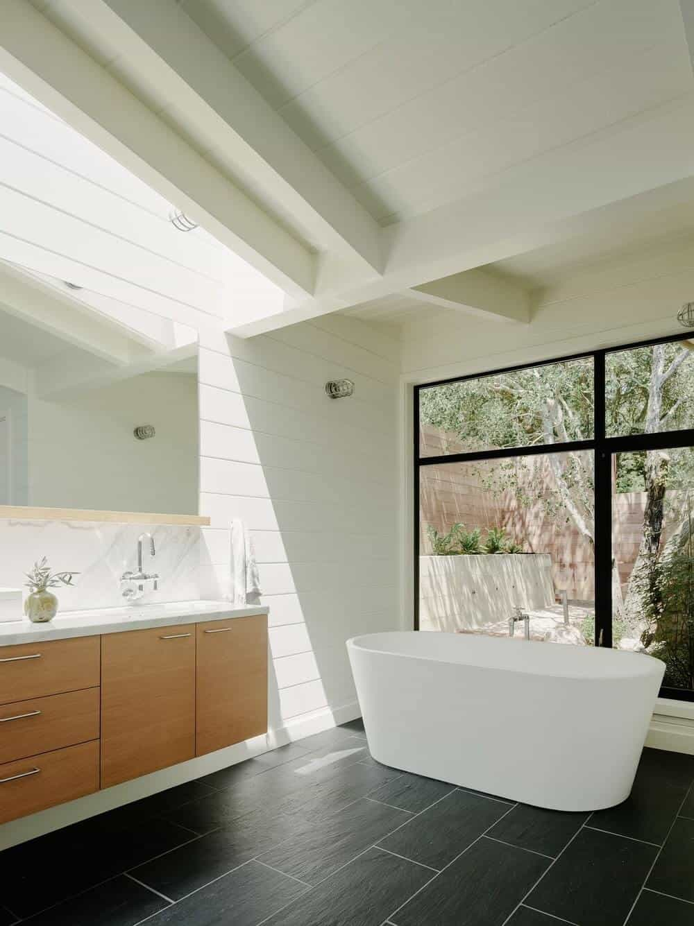 This primary bathroom features a modern pedestal tub on the black tiles flooring and a sliding door that leads to the garden. It also has white walls with a large mirror.