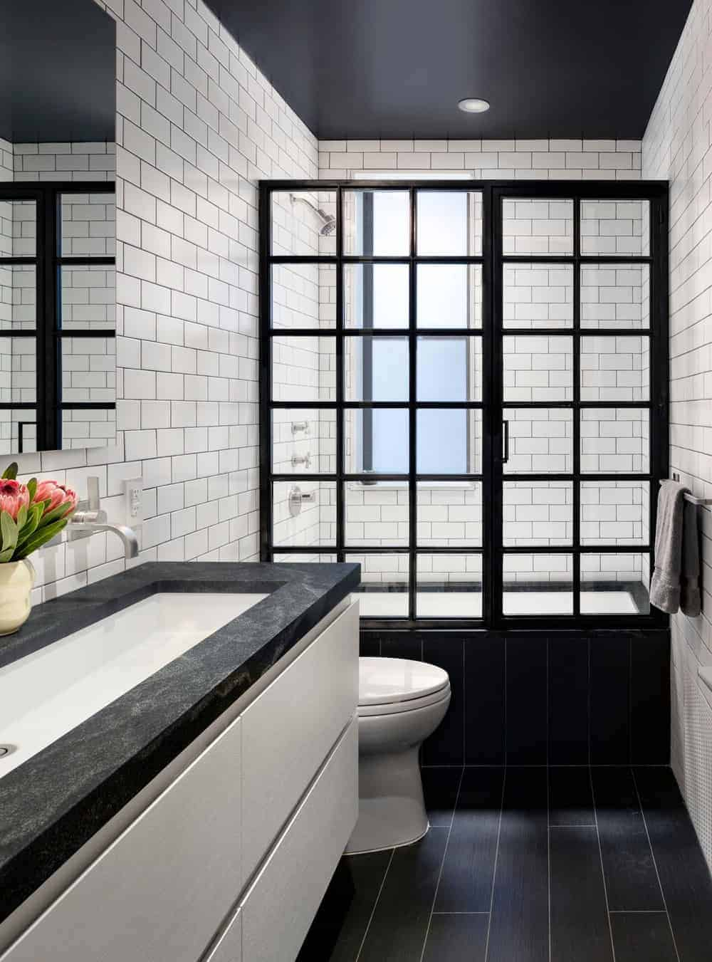 Industrial-style primary bathroom with a toilet and a walk-in shower enclosed in black aluminum framed door. It includes a floating sink vanity that matches the hardwood flooring and whitesubway tilescheme.