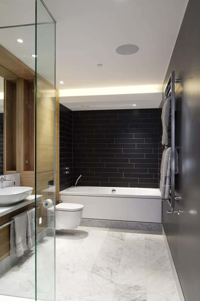 The primary bathroom featuring a light tones courtesy of a stained hardwood flooring and corner tub with a large black format wall tiles.