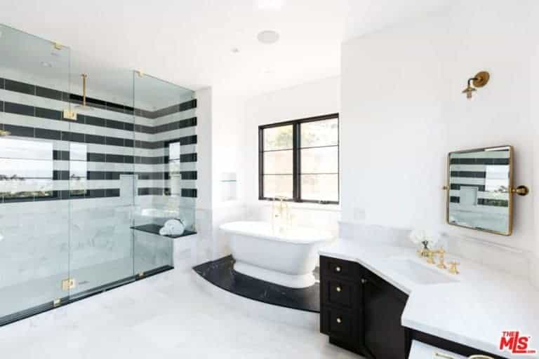 This primary bathroom features white tiles and white walls with windows with a great view outside. It also has a tub on black marble and black cabinet.