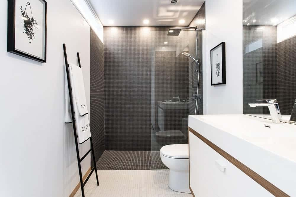 A gorgeous bathroom with a traditional toilet on the white flooring tiles with a glass-door shower standing over black flooring and wall tiles.