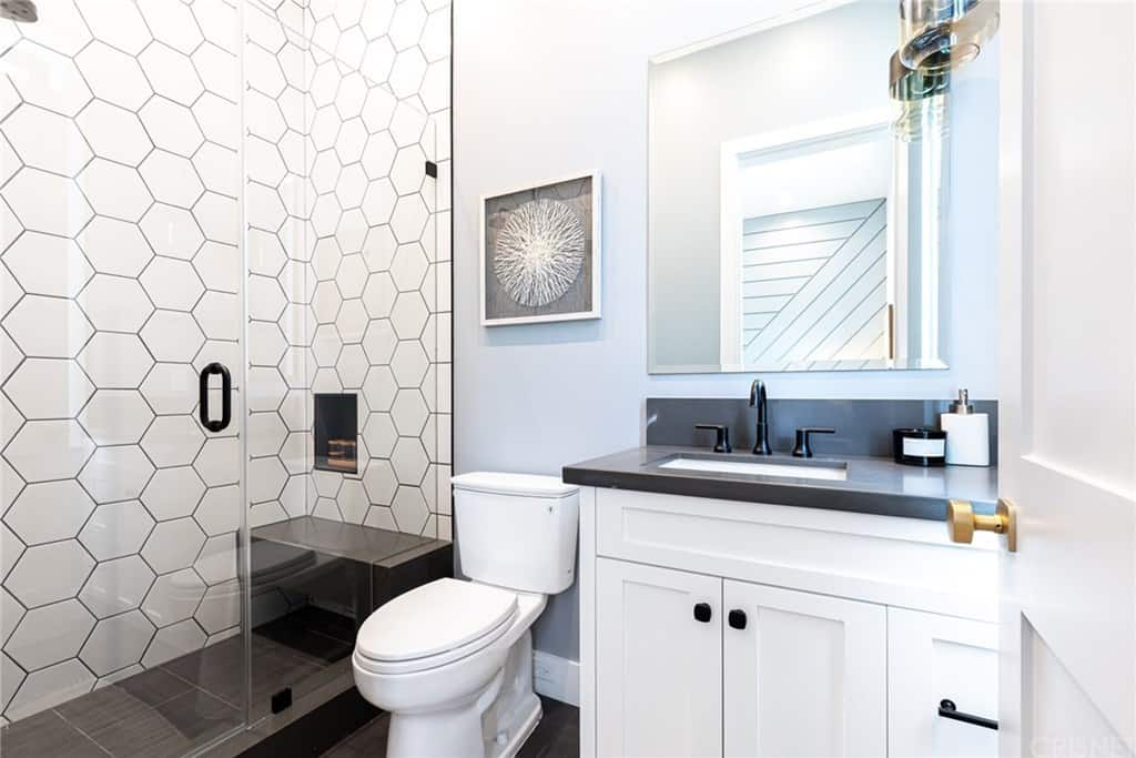 The black and white bathroom contrasts over dark large format tile flooring, with a glass enclosure shower and vanity with smoked-glass cupboards.