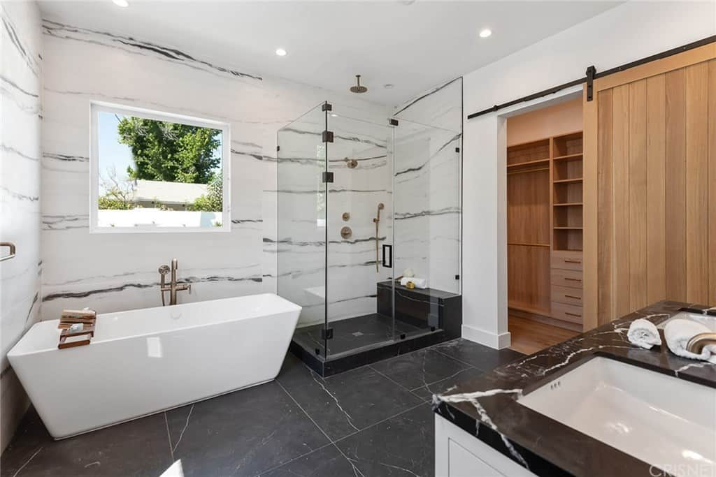The modern primary bathroom features a freestanding tub complemented and a walk-in shower enclosed in the glass door.