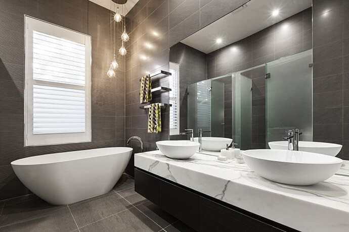 The bathroom has vessel sinks on top of chic white marble, creating a distinct meditative feeling. The lighting fixtures drop down from the ceiling towards the bathtub with a soft autumn glow.
