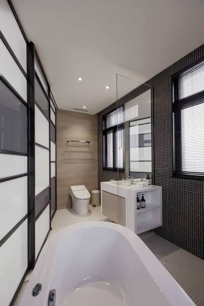 The bathroom is filled with sharp detail, including micro-tile flooring and wall, with a large soaking tub sharing space with a bold white floating vanity.