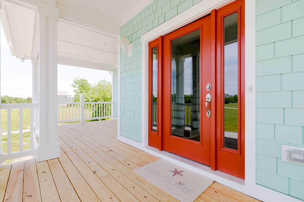 A spacious porch with wide plank flooring and a red framed front door that stands out against the mint green brick walls.