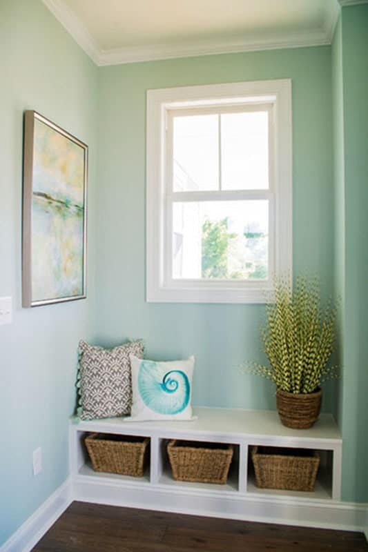 On the right is the foyer showcasing a lovely artwork and a built-in window seat nook with wicker baskets underneath.
