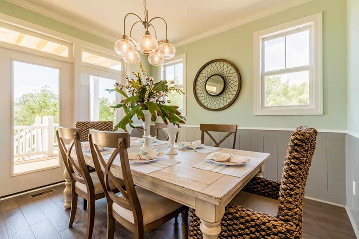 The dining area is designed with gray wainscoting and a stylish round mirror flanked by white framed windows.