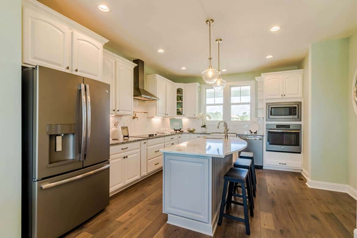 Ambient lighting continued in the kitchen. White cabinets and stainless steel appliances run throughout the area.