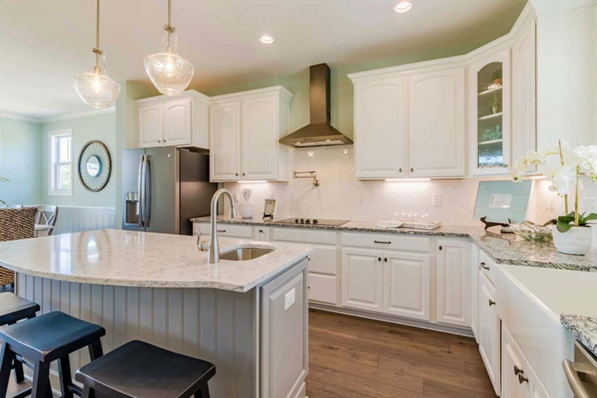 A marble top beadboard island in light gray sit in the middle of the kitchen. It is illuminated by a pair of glass pendants and fitted with an undermount sink.