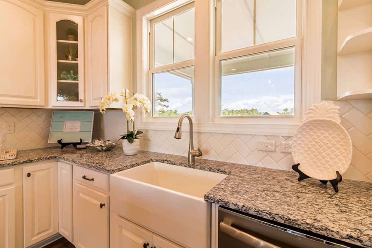 The kitchen includes granite countertops contrasting the white cabinets and farmhouse sink along with the backsplash arranged in a herringbone pattern.
