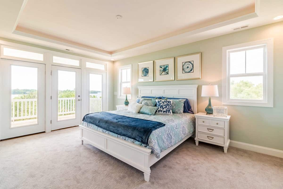 The bedroom includes a beautiful tray ceiling and a glass door that opens to the balcony.