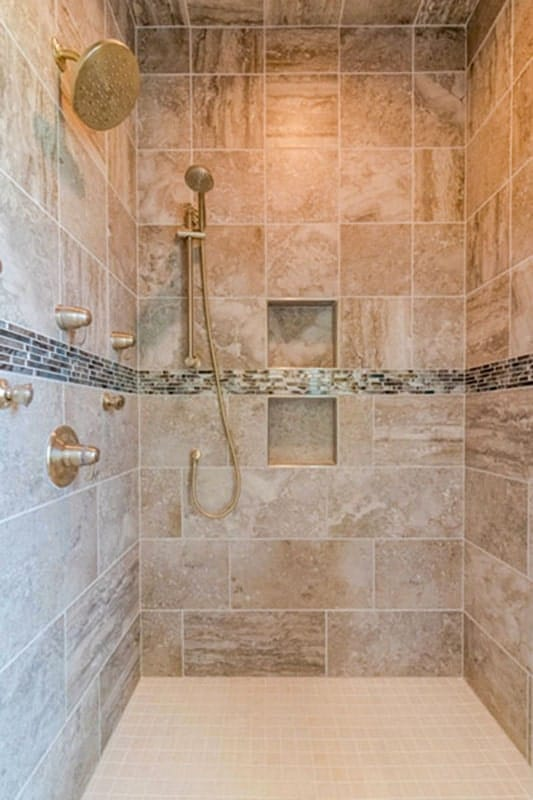 The bathroom has brass fixtures and tiled walls fitted with a pair of inset shelves.