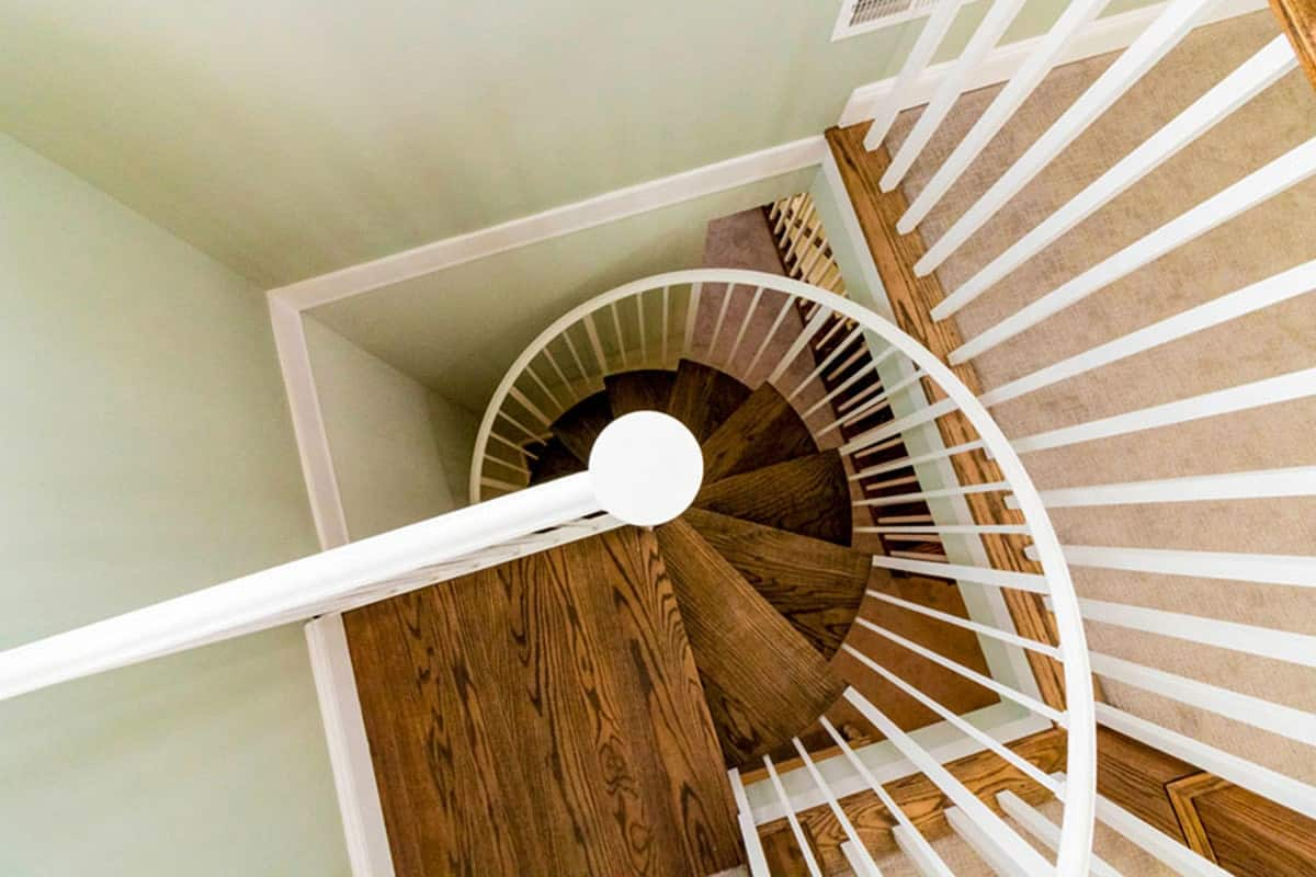 Top view of the spiral staircase with natural wood treads and white railings.
