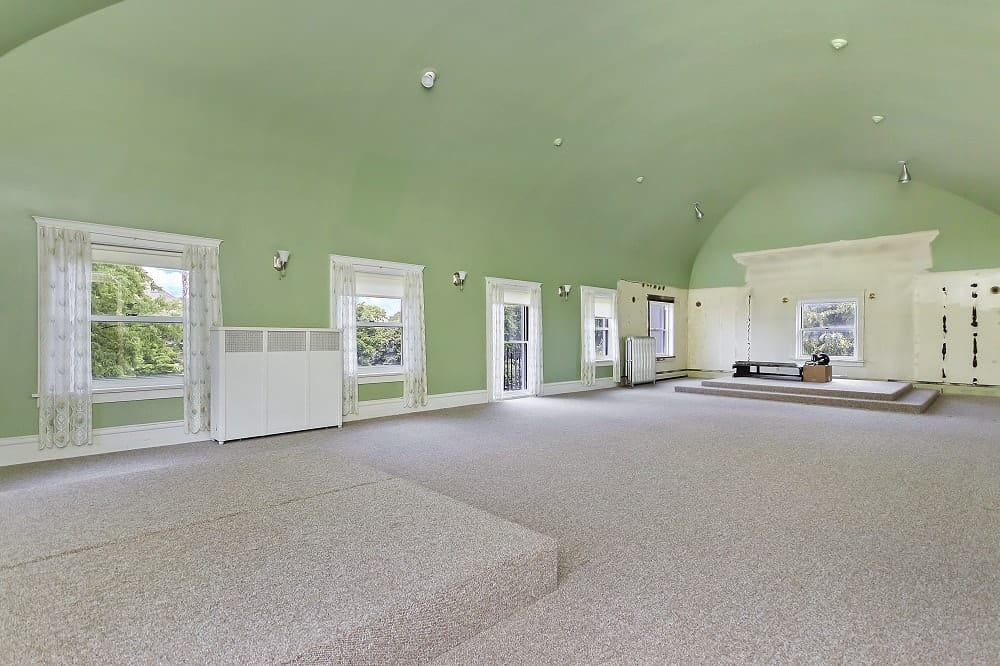 The gorgeous ballroom of the third floor has a green cove ceiling converging with the walls complemented by the spacious gray carpeted flooring with elevations for a stage. Images courtesy of Toptenrealestatedeals.com.
