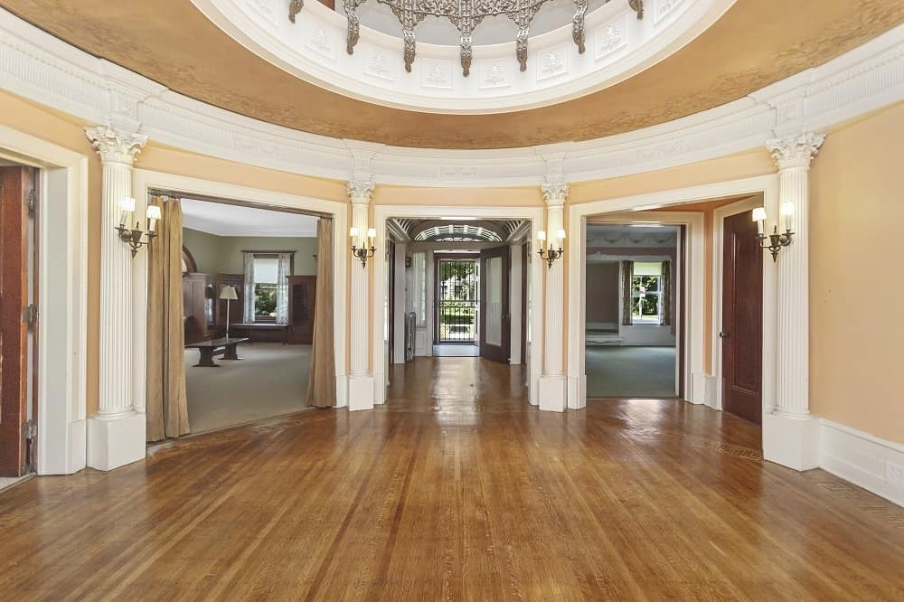 The large round foyer has charming hardwood flooring and beige walls. Images courtesy of Toptenrealestatedeals.com.