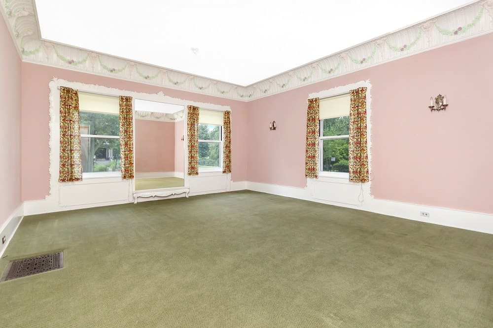 The large and airy living room has an abundant supply of natural lighting that works well with its charming pink walls. Images courtesy of Toptenrealestatedeals.com.