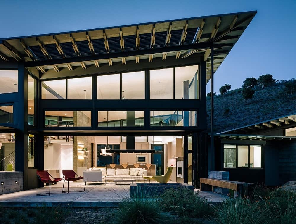 View of the house interior from the outside at night of the Butterfly House designed by Feldman Architecture.