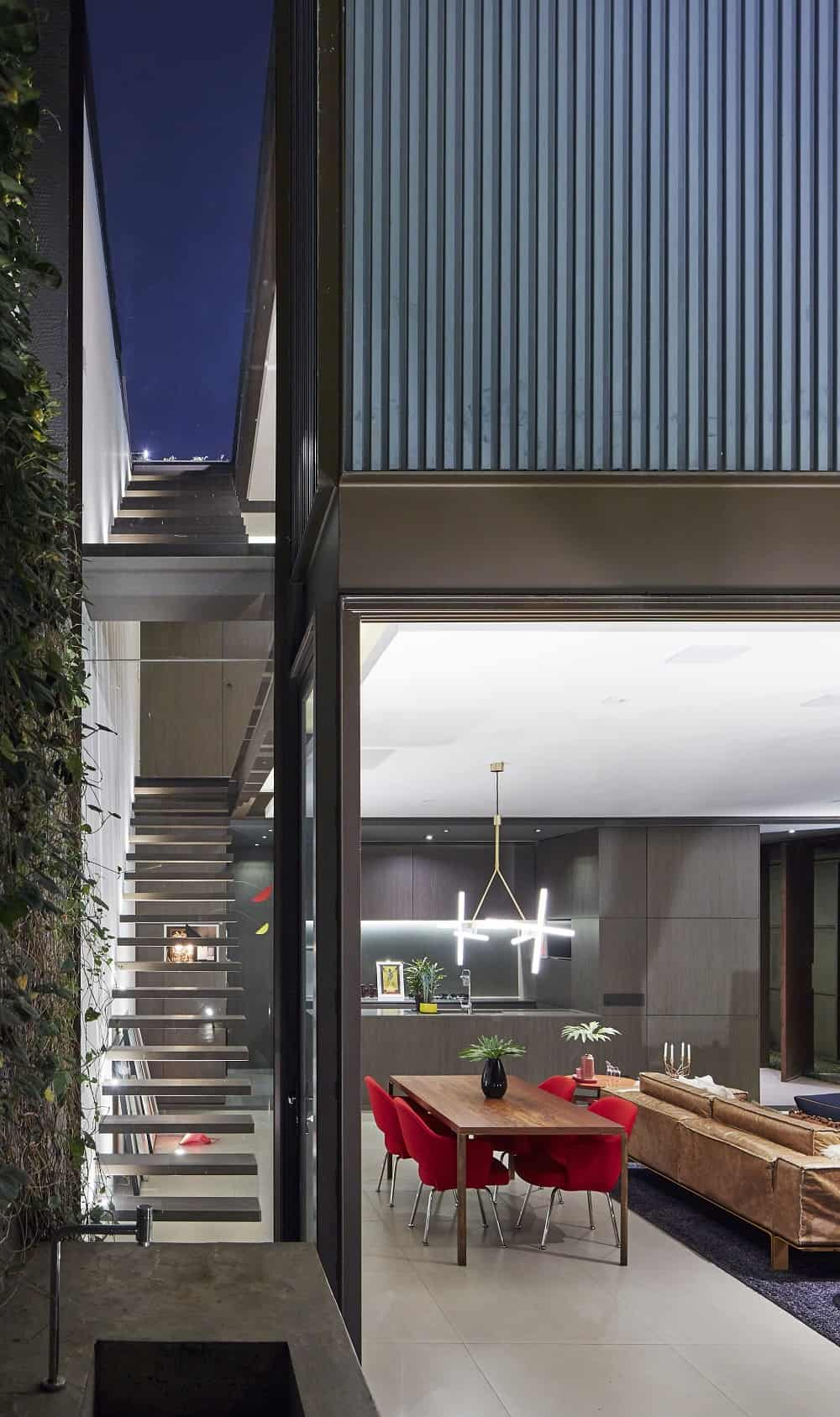 Dining area and kitchen beside the floating staircase in the Casa Box designed by Flavio Castro.