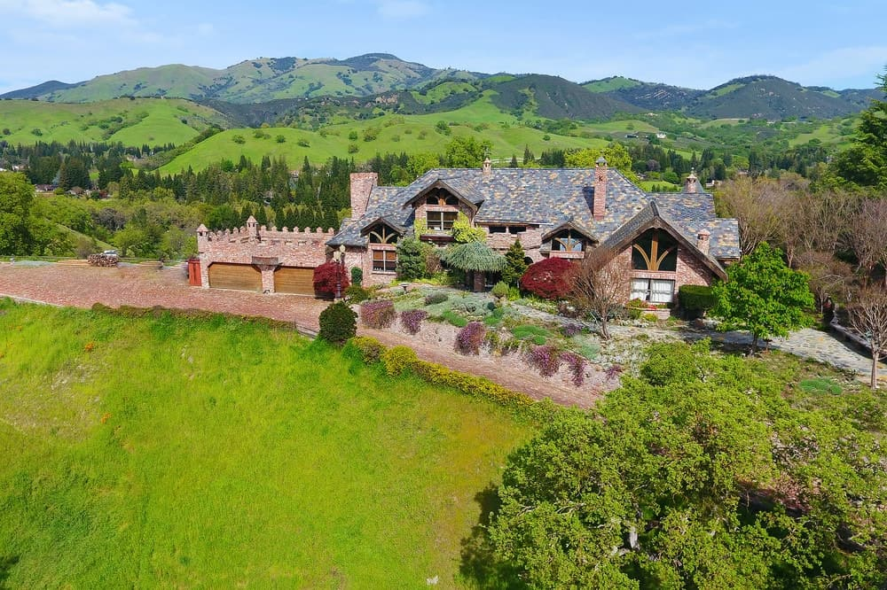 An aerial view of the charming castle-like mansion surrounded by lush greenery that complements its earthy tones filled with bricks and and chimneys. Images courtesy of Toptenrealestatedeals.com.