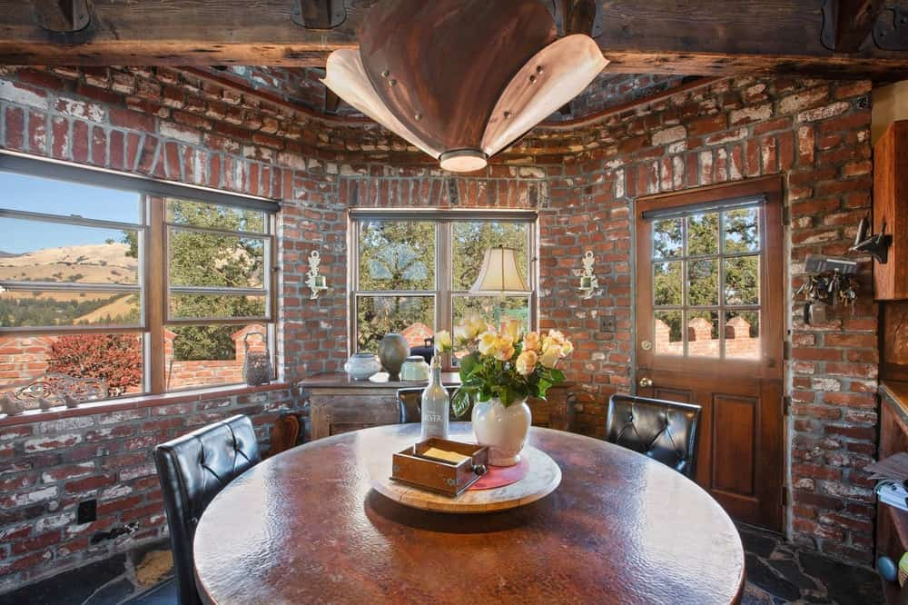 The mansion also has an informal dining area with a round wooden dining table surrounded by leather upholstered chairs brightened by the surrounding glass windows and wooden door fitted with glass panels. Images courtesy of Toptenrealestatedeals.com.