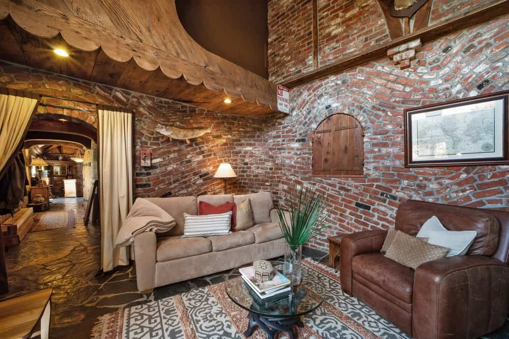 This simple and rustic living room is complemented by the gorgeous undulating red brick walls that set a lovely background for the sofa and leather arm chair. Images courtesy of Toptenrealestatedeals.com.