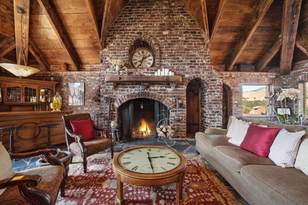 This great room is fitted with another living room that is warmed by a gorgeous brick fireplace topped with a clock embedded into the wall. This is matched by the beautiful clock that doubles as a coffee table in the middle of the sofa set. Images courtesy of Toptenrealestatedeals.com.