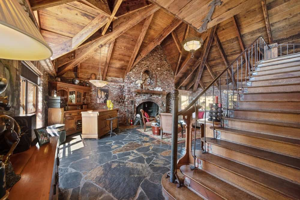 This farther view of the living room shows that it is just beyond the stairs and it has a wide stone flooring that is augmented by a tall arched wooden ceiling with exposed wooden beams. Images courtesy of Toptenrealestatedeals.com.