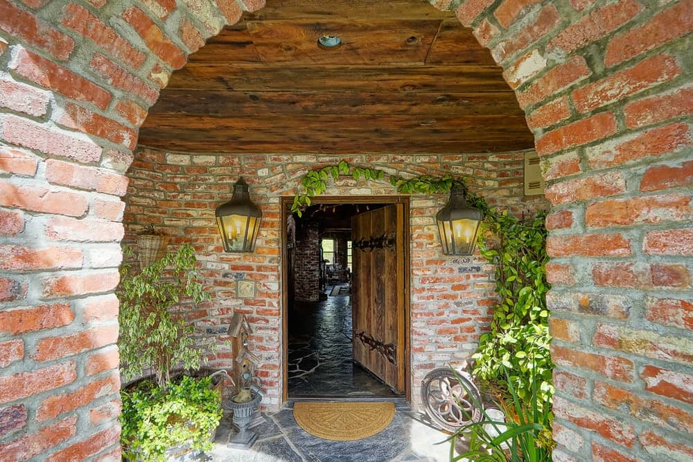The main entry of the castle-like mansion is complemented by the brick walls and arch adorned with potted plants and creeping vines as well as a couple of charming wall-mounted lamps flanking the wooden main door. Images courtesy of Toptenrealestatedeals.com.