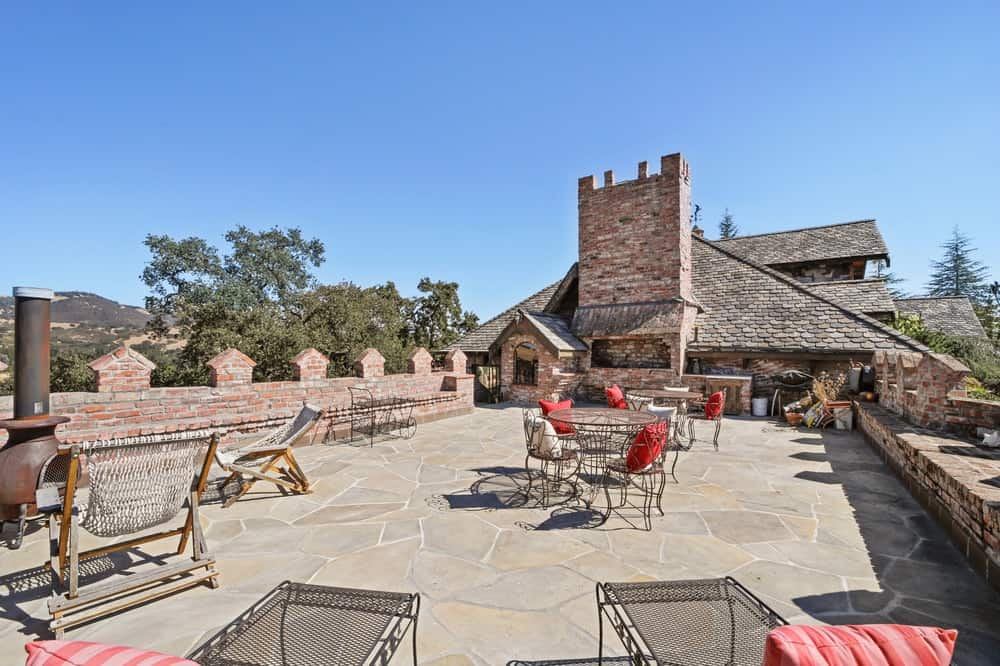 The rooftop patio has a wide stone floor space with an outdoor cooking area, outdoor dining area and a sitting area that is warmed by a freestanding iron furnace. Images courtesy of Toptenrealestatedeals.com.