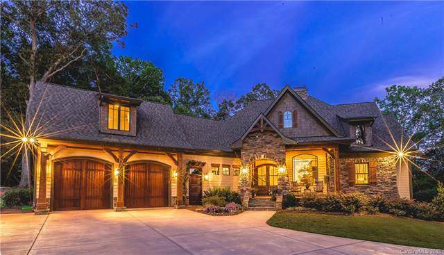 This charming Craftsman-style cottage has gorgeous dark gray roofs that is complemented by the amber glow of the exterior walls filled with wall-mounted lamps, dark wooden doors and stone wall accents paired with a simple landscaping.