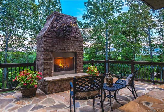 This cottage has a warm and comfortable outdoor stone fireplace flanked by a couple of potted plants and paired with two wrought iron patio chairs and a small side table with a nice background of the surrounding tall trees. Source: TheHouseDesigners.com
