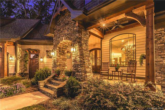 The main entry is foregrounded with a charming stone arch adorned with a couple of wall-mounted lamps. This view also glimpses the small porch that has a couple of outdoor chairs illumintaed by the warm glow of the large arched window. Source: TheHouseDesigners.com