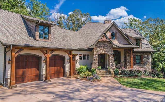 This daylight view shows that the dark wooden garage doors are paired with wooden support columns with a dormer window above. There are also wooden support columns at the main entry area for the ceiling of the porch. Source: TheHouseDesigners.com
