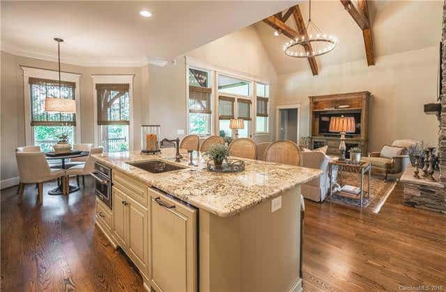 A few steps from the living room is the kitchen island that has a darker beige tone than the walls and ceiling and has an earthy marble countertop. This makes it stand out against the dark hardwood flooring. This view also shows the beautiful arched ceiling of the living room with exposed wooden beams and a round chandelier. Source: TheHouseDesigners.com