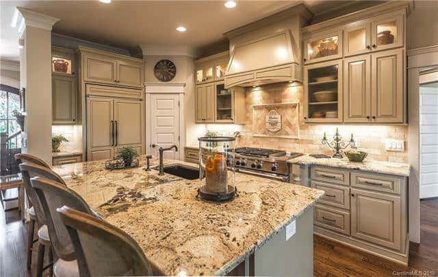 The kitchen cabinetry has the same tone as the kitchen island and has an elegant design to its cabinets doors and drawers. These are complemented by the warm glow of the backsplash from the spotlights under the vent hood of the cooking area. Source: TheHouseDesigners.com