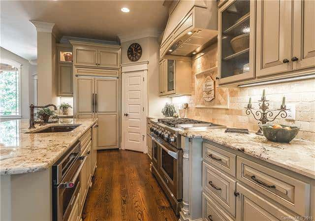 The dark hardwood flooring of the kitchen matches well with the tone of the cabinetry topped with a beige ceiling that has recessed lights throwing off a warm yellow glow. Source: TheHouseDesigners.com