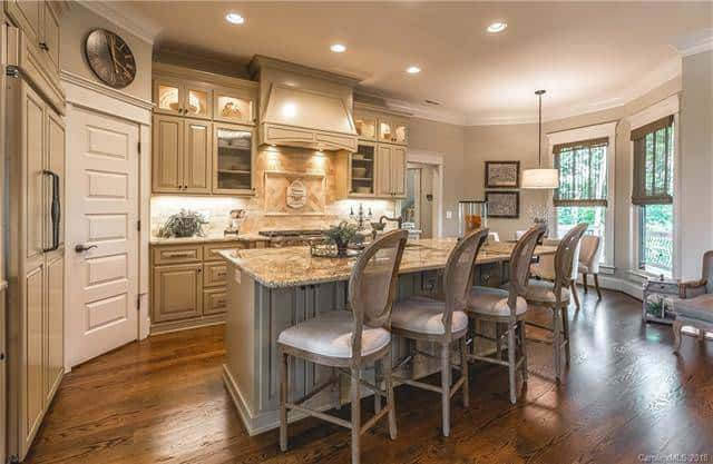 The kitchen island is paired with three cushioned chairs for a breakfast bar illuminated by the recessed lights of the ceiling. On the far end is the informal dining area. Source: TheHouseDesigners.com