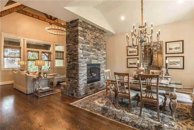 On the other side of the stone fireplace of the living room is the formal dining room using the same stone pillar for warmth. This charming stone pillar matches well with the patterned area rug of the dining room that tops the dark hardwood flooring. Source: TheHouseDesigners.com