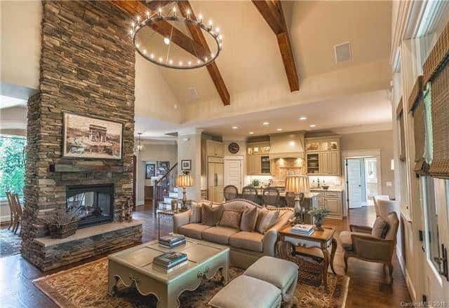 This is a wide view of the great room from the corner of the living room. Here you can see that the open area houses the living room, kitchen, informal dining area as well as the formal dining area at the other side of the stone fireplace. Source: TheHouseDesigners.com