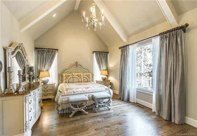 The primary bedroom has a tall cathedral ceiling with the same beige tone as the walls hanging a chandelier in the middle. The light of this chandelier is augmented by the large window on the side that bathes the elegant bed and hardwood flooring with natural lighting. Source: TheHouseDesigners.com