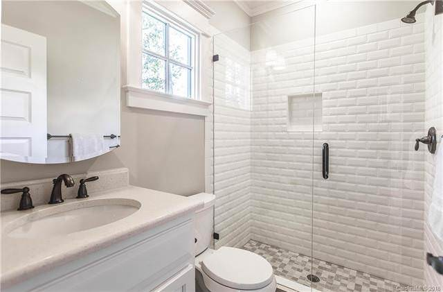 This simple bathroom has textured white tiles for the walls of the glass enclosed shower area. This is beside the white toilet under the small window and its other side is the simple vanity with a neutral tone to match the walls and ceiling. Source: TheHouseDesigners.com