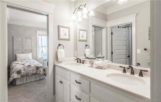 The bathroom of this bedroom has a large two-sink vanity with a large wall-mounted mirror topped with wall-mounted lamps that also illuminate the light countertop. Source: TheHouseDesigners.com