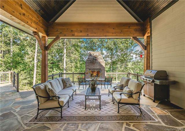 The beautiful outdoor patio has a tall wooden cathedral ceiling shading the charming wrought iron patio sofa set that has an awesome view of the surrounding greenery and tall trees. Source: TheHouseDesigners.com